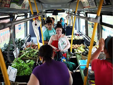Volunteers help people pick through fresh vegetables and fruit on the new MarketMobile bus, that was introduced at Morrison Gardens on Saturday, July 26, 2014. (Cole Burston/Ottawa Citizen)